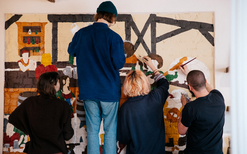 Four creatives from NUA standing next to each other, all painting sections of a mural design for a pub wall
