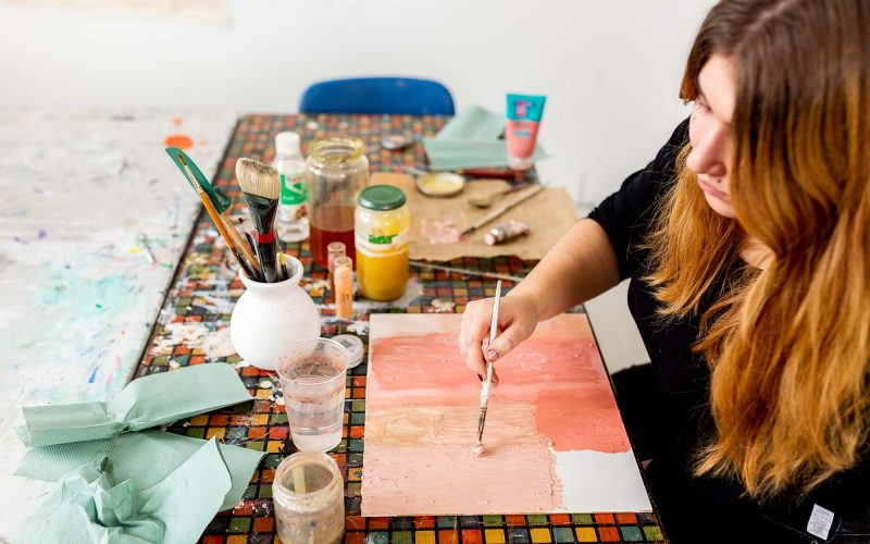 Student working on a painting, holding a paint brush surrounded by art material